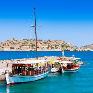 Tourist and fishing boats at the pier of the village of Plaka, near the island of Spinalonga. Crete
