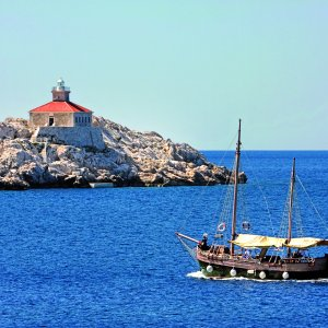 Old wooden sailboat and the lighthouse